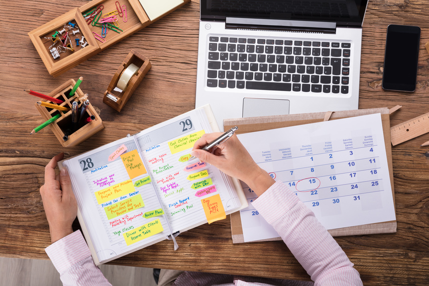 Businesswoman Writing Schedule In Calendar Diary