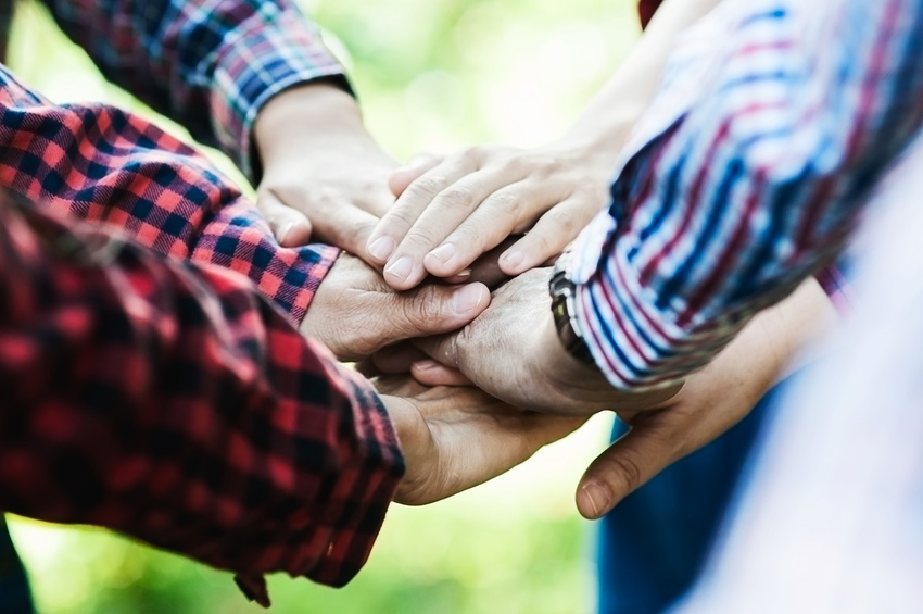 People group join hands together as teamwork unity symbol during their meeting activity to achieve their ultimate goal. Vintage tone close up at join hands over blur soft light green garden background